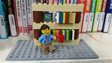 Lego man holding a cup standing in front of books